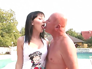 Spoiled brunette wench is sucking small dick of aroused grandpa by the poolside