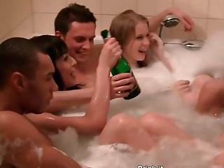 Cheerful folks maul each other in a hot tub filled with foam